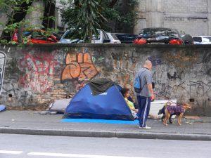 Tältande mamma på trotoar i Sao Paulo. Man med hundar stannar och kollar att allt är ok.